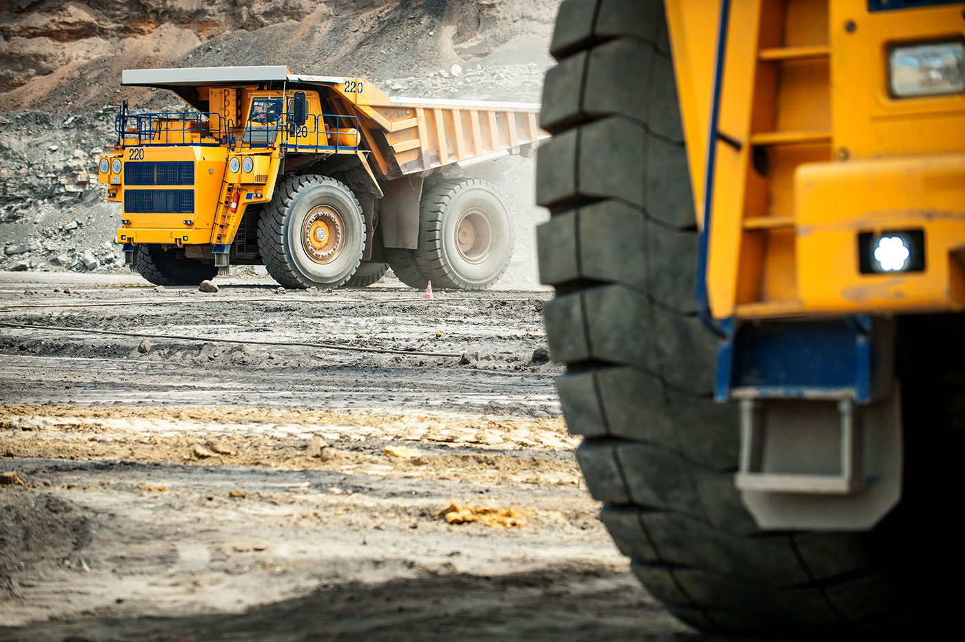 Acme OEM Mining | Two large yellow mining trucks onsite