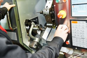 Close-up of an engineer drilling hole or boring detail on metal cutting machine tool at manufacturing factory